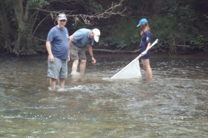 Whit and Kaylee collecting our sample. Chris watches the timer.